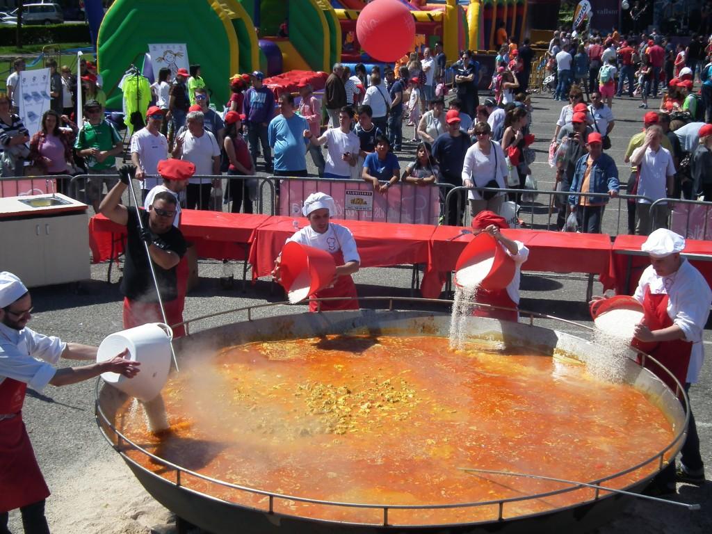 añadiendo arroz en la paella gigante