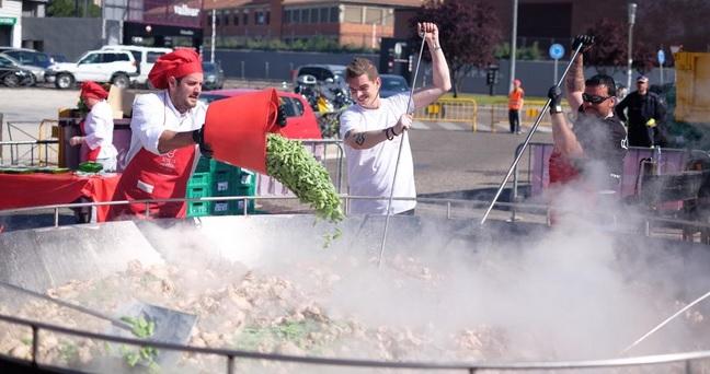 añadiendo judías verdes en la paella gigante