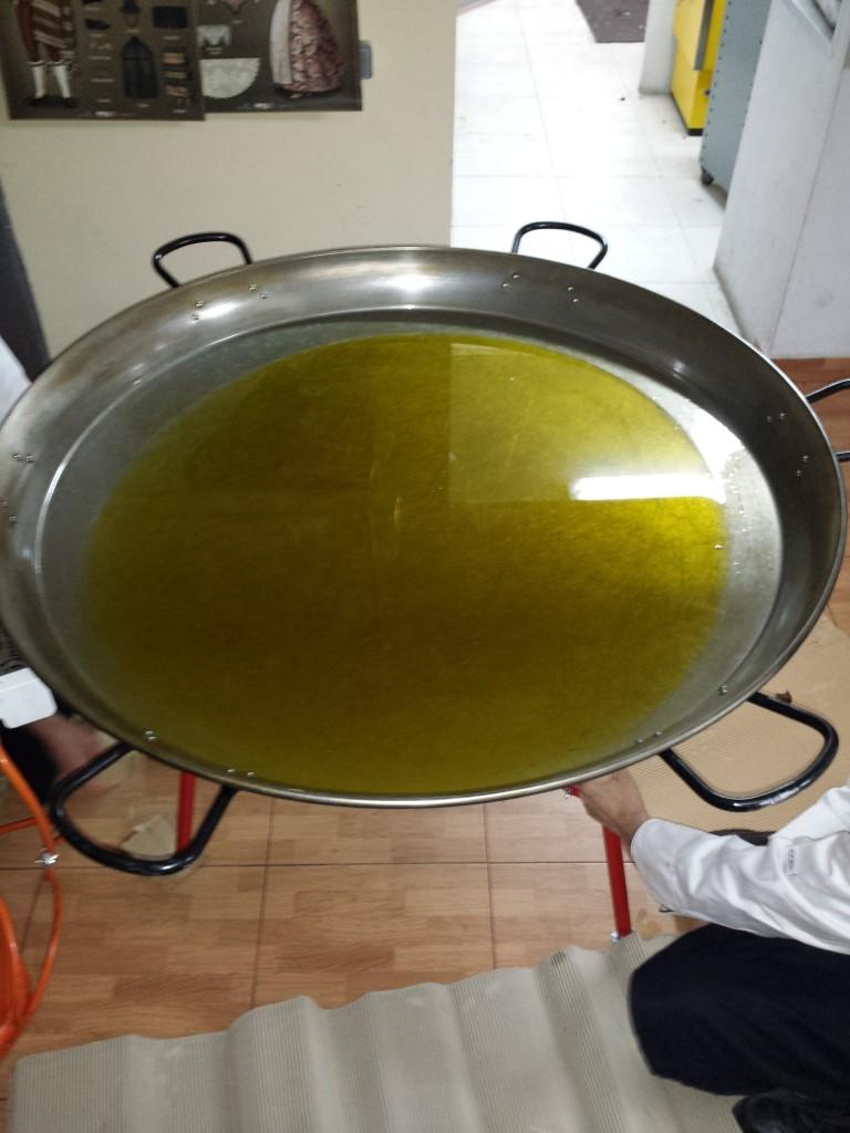 paella para 200 personas añadiendo aceite